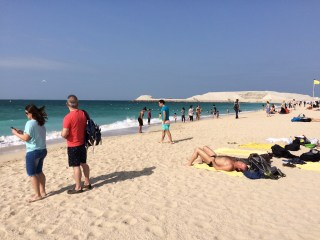 Visitors enjoying the sand and waters of the Arabian Gulf.