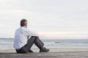 Businessman sitting on beach looking at ocean