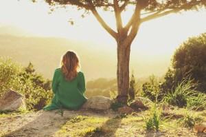 Women sitting on cliff next to tree in the sunlight - Karen Lewis Social Worker