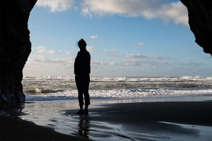 Lady looking at ocean from the beach