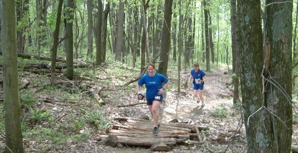 two women running through a forest