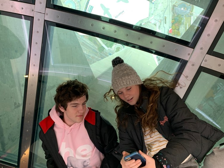two teenagers lying on a glass floor in the CN Tower 553m above the city