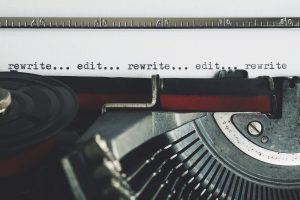 """typewritten words in an old typewriter, saying """"rewrite... edit... rewrite... edit"""""""