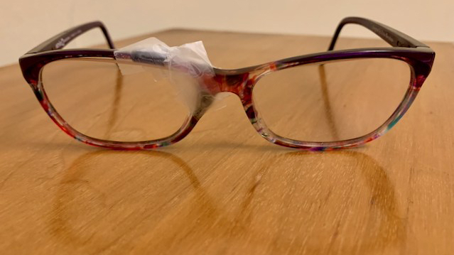 red glasses with electrical tape, glue, and clear tape holding them together