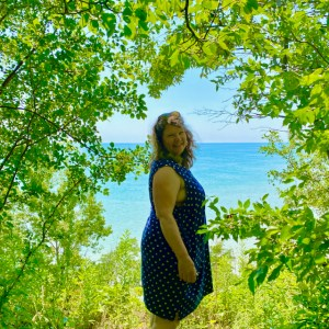 me (54-year-old woman with brown hair) wearing a blue polka-dot dress, smiling amongst greenery overlooking blue water