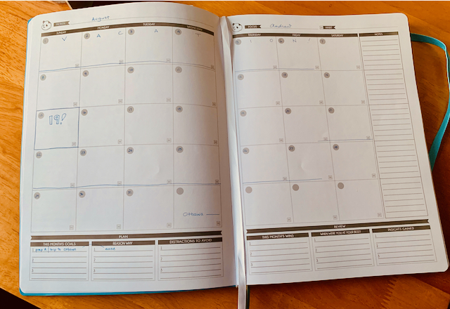 Open planner page with a month schedule, mostly blank, showing a week of vacation.