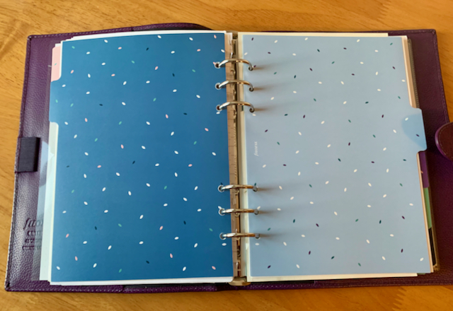 Medium size 6-ring binder with colourful dividers showing.