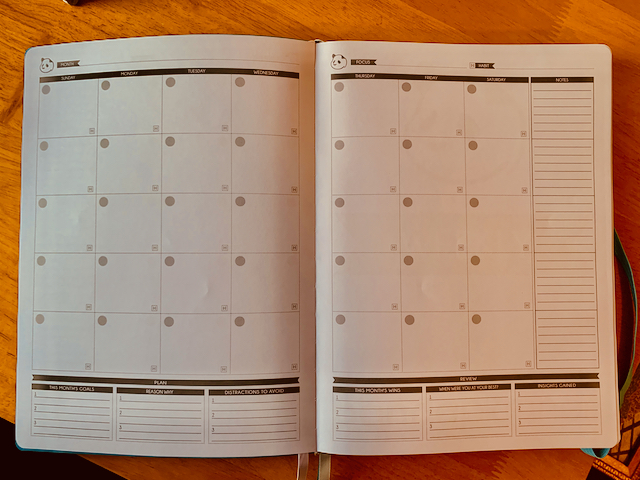 Blank desk-size planner notebook open to a full month view.