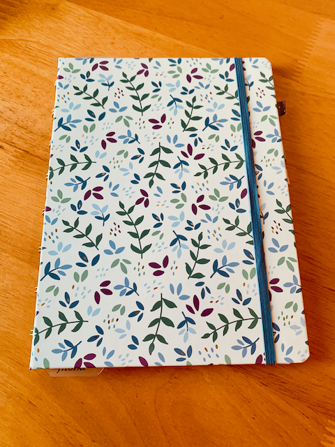 Medium-size notebook with colourful leaves on the front.