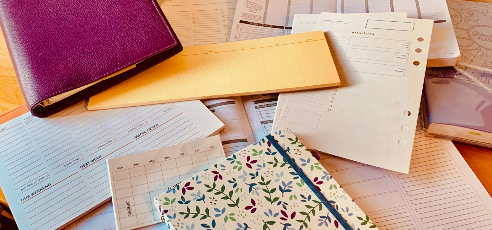 Messy pile of calendars, planners, sticky notes, and pads with a 'week-at-a-glance'.