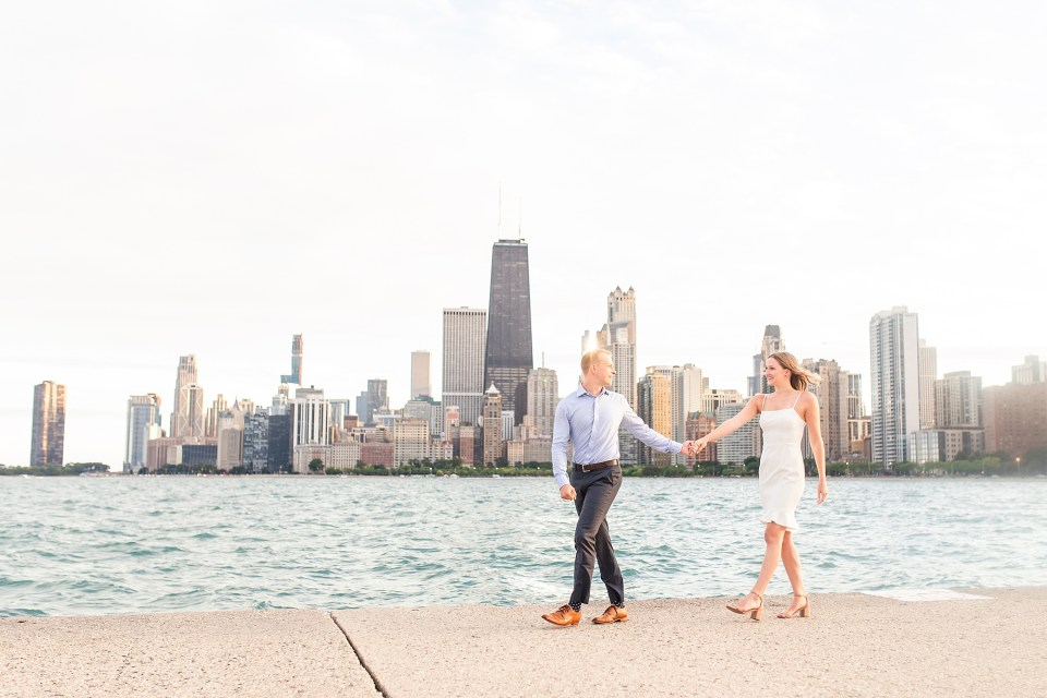 Beautiful couple at North Avenue Beach walking with Chicago Skyline engagement photos by Karen Shoufler Photography