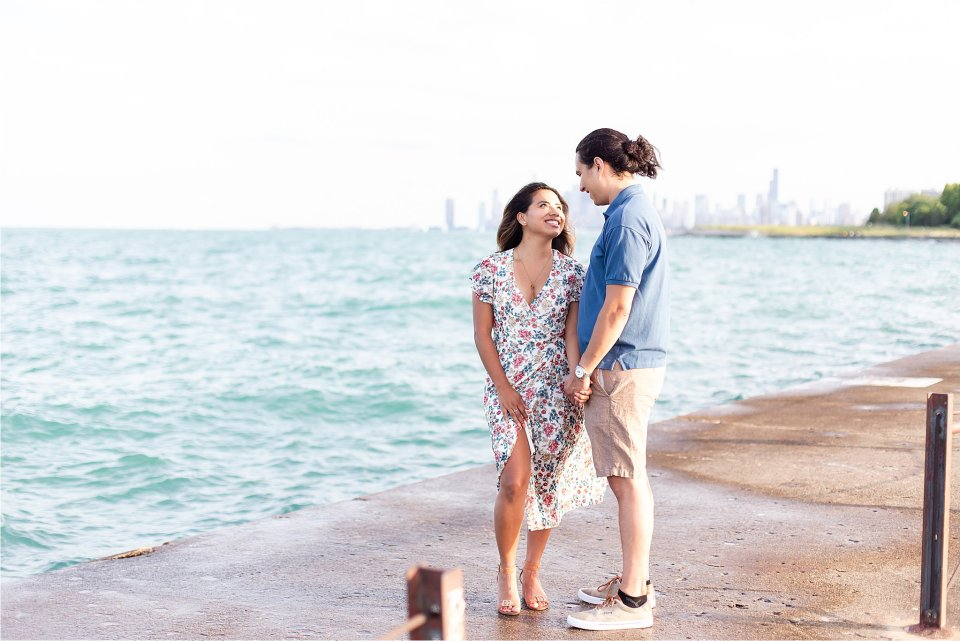 Sweet, romantic photo of engagement session at Montrose Beach with Chicago Skyline by Karen Shoufler Photography
