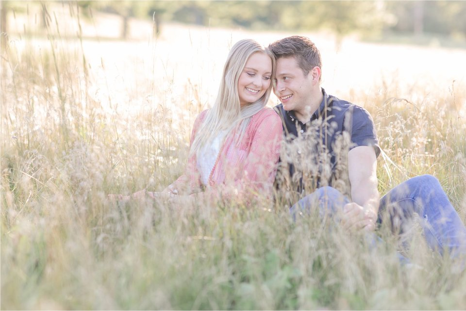 Engaged couple sitting in grass at Donovan Park in Peoria for engagement session