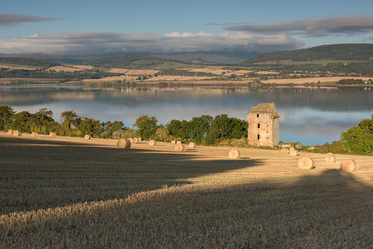 Black Isle photography - ruined castle in a field with shadows and straw bales in the foreground, with water and hills beyond
