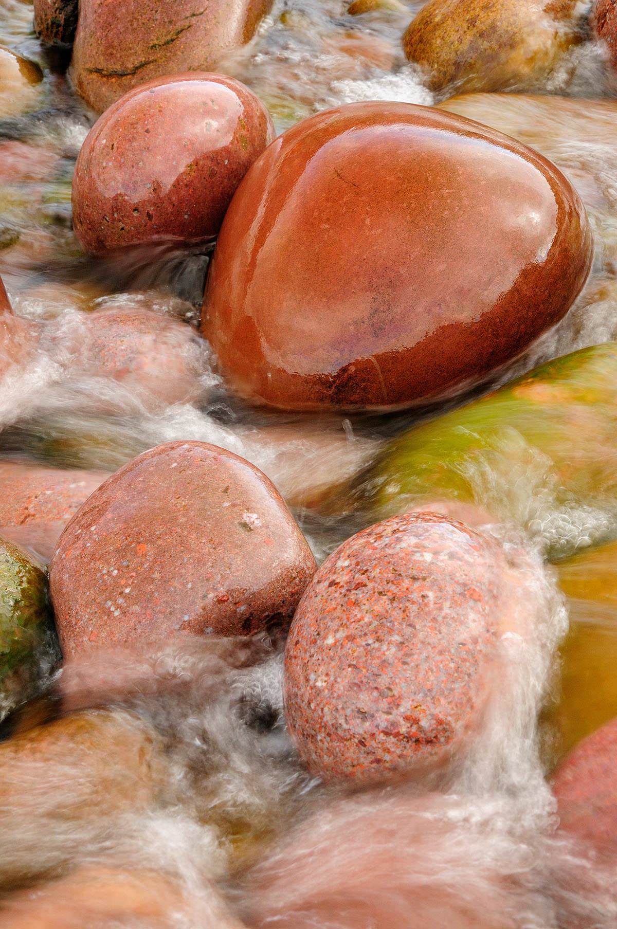 Brown and pink granite stones in a stream with water flowing over the rocks