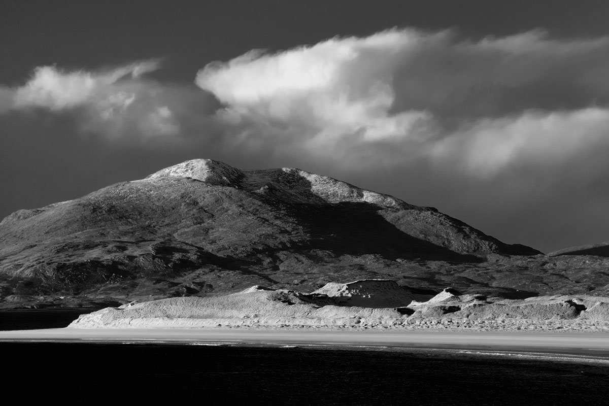 Monochrome image of a beach on a Scottish island with tall sand dunes and a snow-capped mountain behind and clouds in the sky