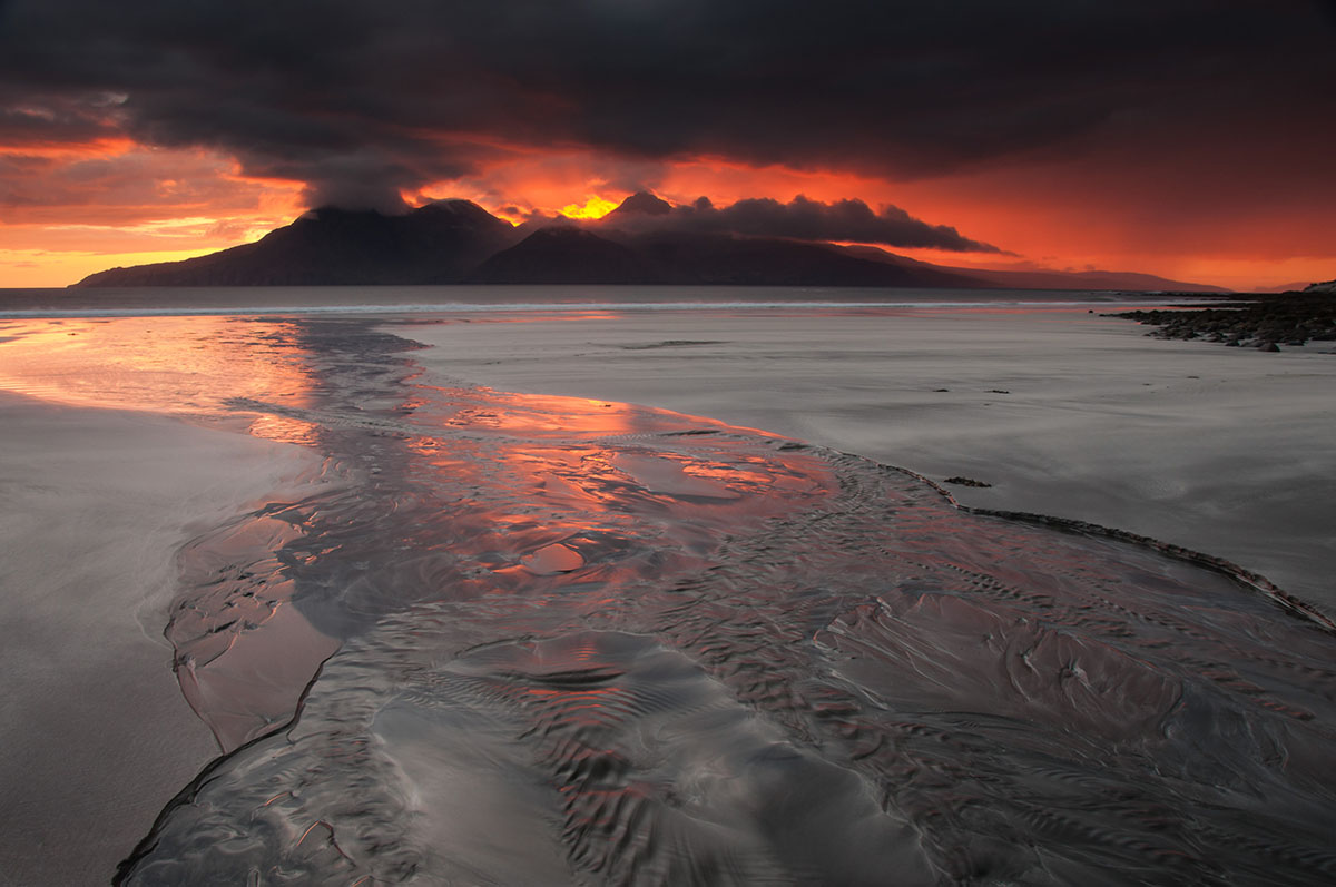 Dramatic sunset over a mountainous island, photographed from a beach with a stream running through it, reflecting the sunset