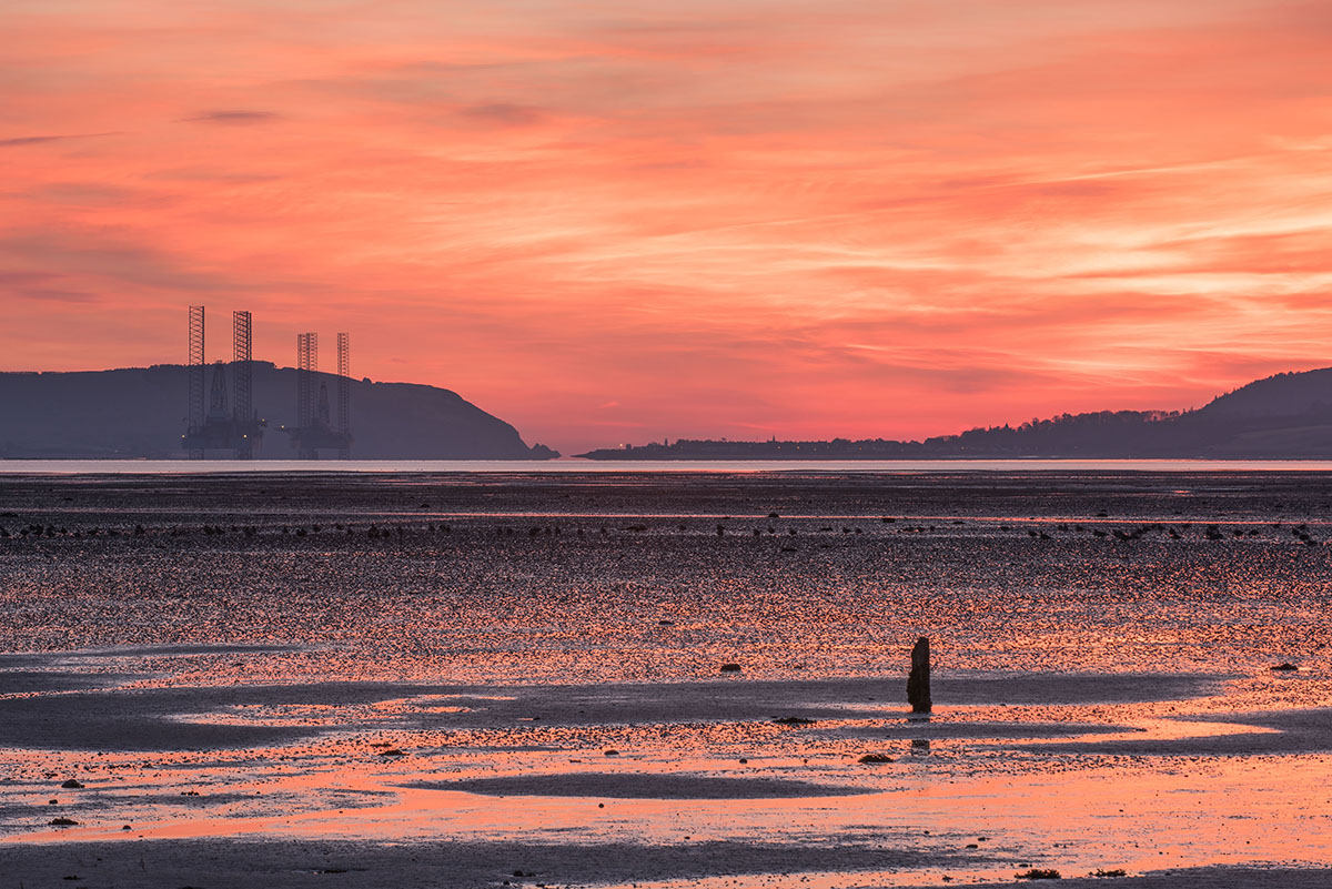 Black Isle photography - post sticking out of mudflat at low tide with oil rigs and hills in the distance under an orange sky