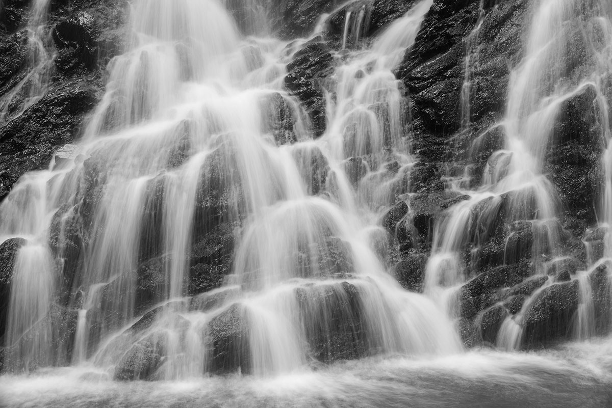 Black Isle photography - monochrome close-up of a waterfall with water flowing over dark rock in slow motion