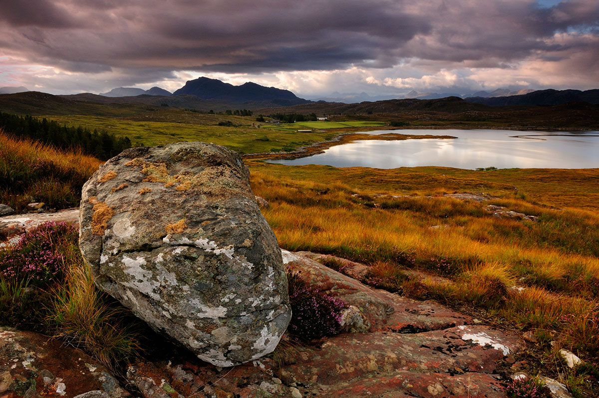 Large grey boulder on top of granite on a grass slope overlooking a bay with mountains beyond, under a dramatic cloudy sky