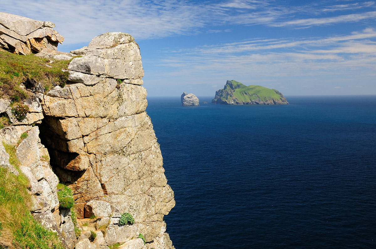 Distant green Scottish island and sea stacks in a blue sea under a blue sky, with a cliff face in the foreground
