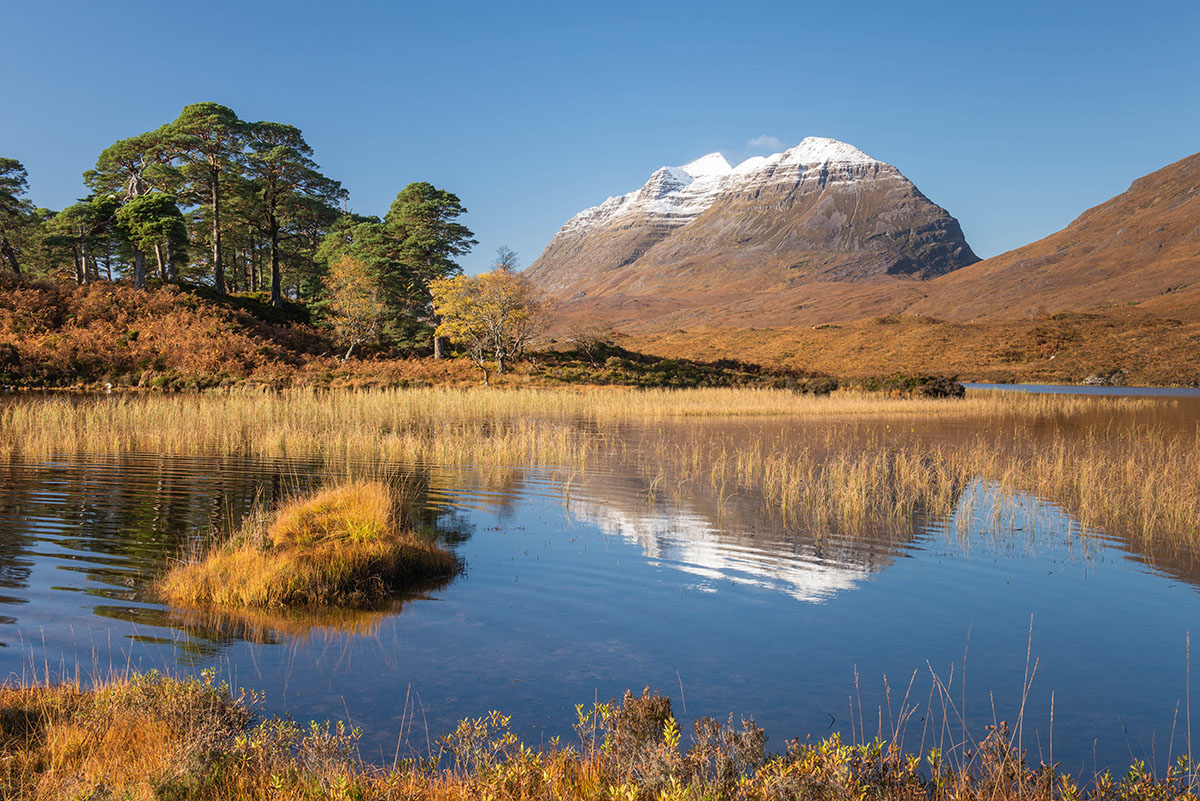Steep sided mountain with snow on its summit behind a Scottish loch and native woodland in autumn colours, beneath blue sky