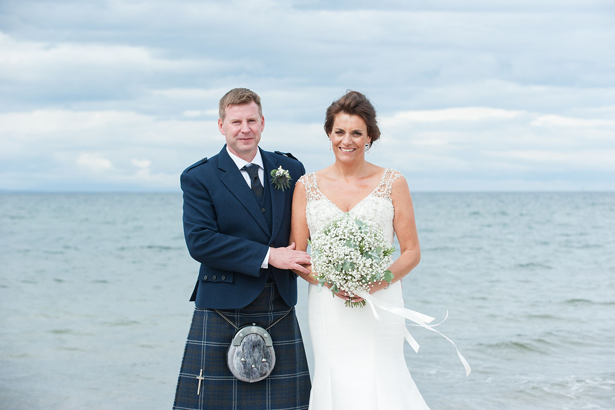 Wedding inspiration - bride and groom standing with the bride holding flowers, with the sea and a cloudy sky behind them