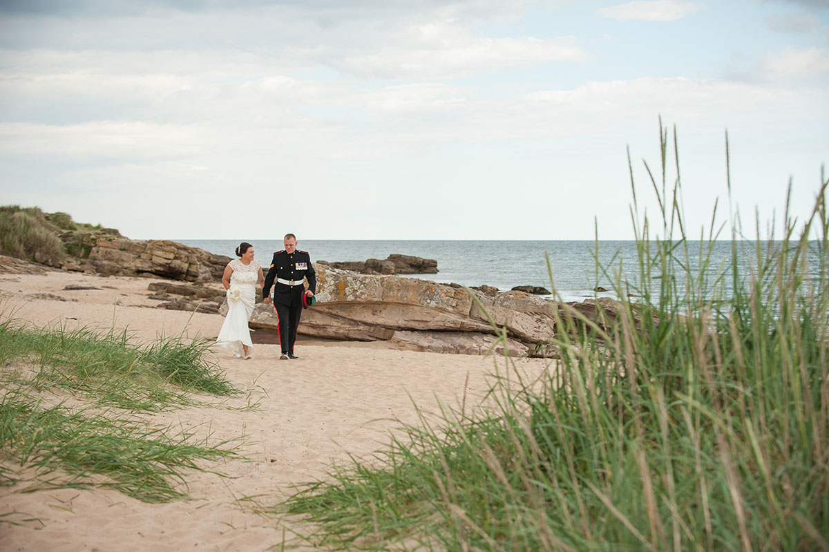 Wedding inspiration - bride and groom in the distance, holding hands next to rocks on a beach, with grass in the foreground