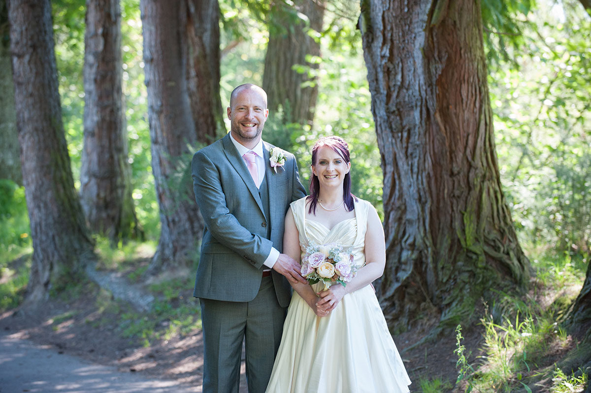 Wedding inspiration - bride in a cream dress and groom in a grey suit smiling and standing in front of tree trunks