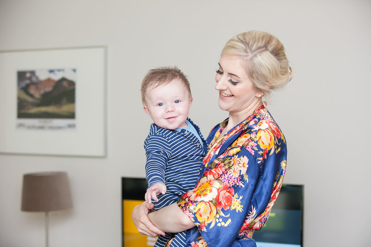 Wedding photo - woman in a floral dressing gown holding a baby boy, dressed in a blue striped onesie and smiling