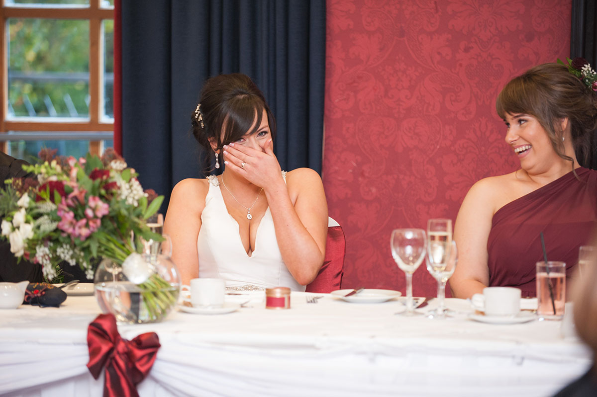 Wedding photo - bride laughing with her hand over her face seated at a table in a room with blue curtains and red walls