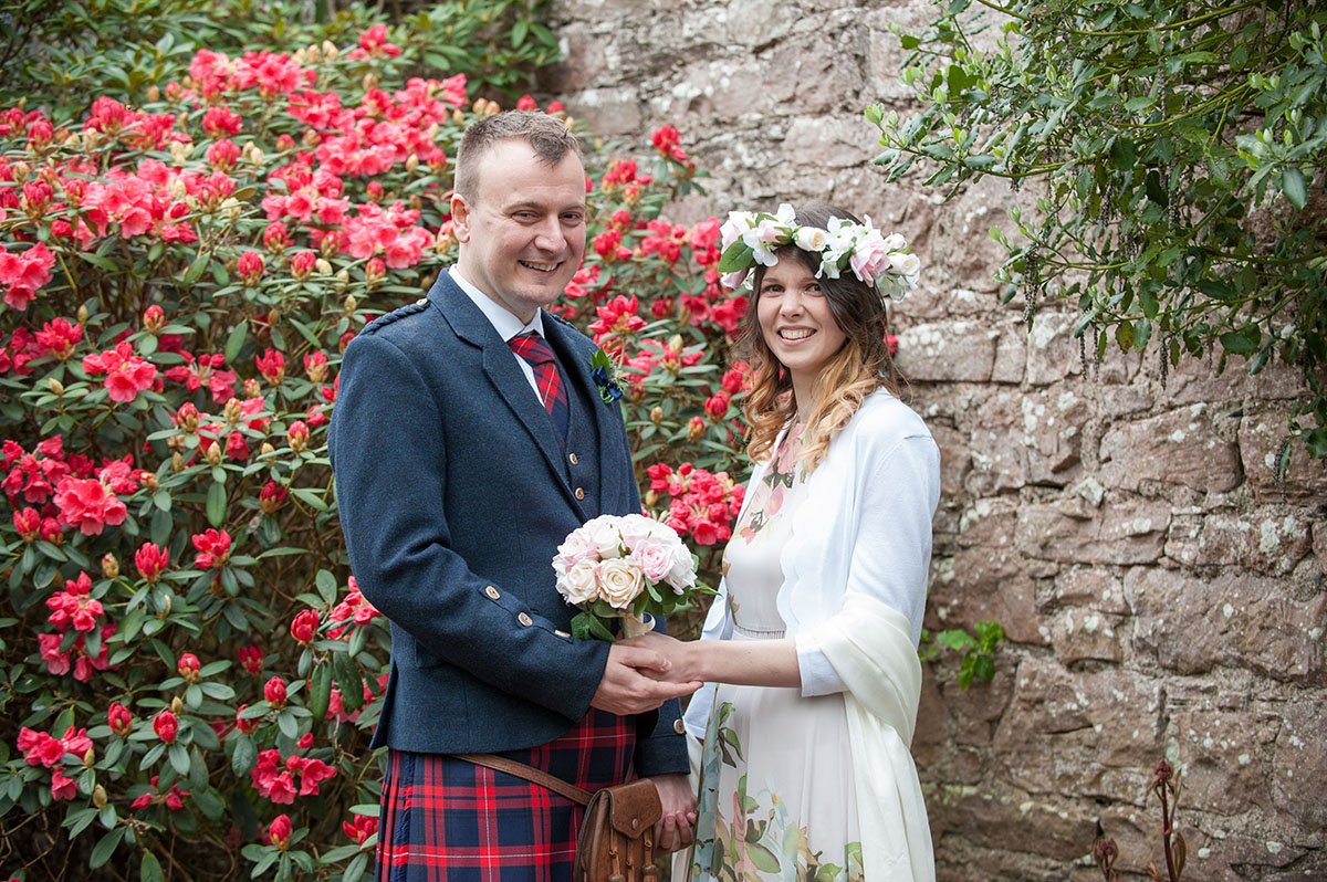 Wedding photo gallery - bride with floral dress and flowers in her hair, standing with a groom in front of red rhododendrons