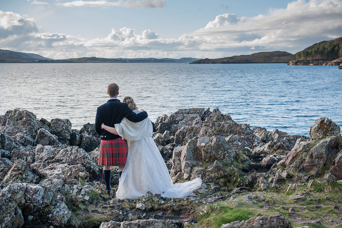 Wedding photo gallery - bride and groom with their arms around each other, standing on rocks and looking out to sea