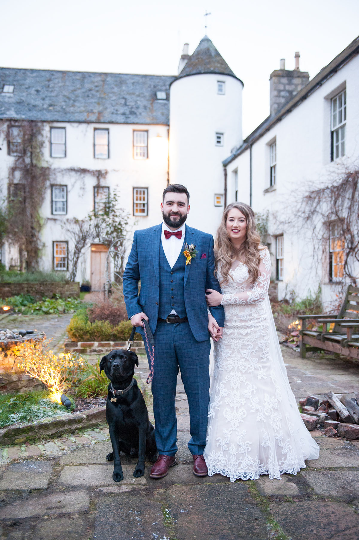 Wedding photography portfolio - bride and groom with a black dog standing in a courtyard in front of a white building