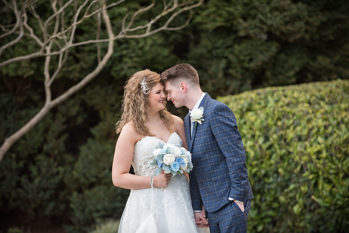 Wedding photography portfolio - bride and groom outdoors smiling at each other with their foreheads touching