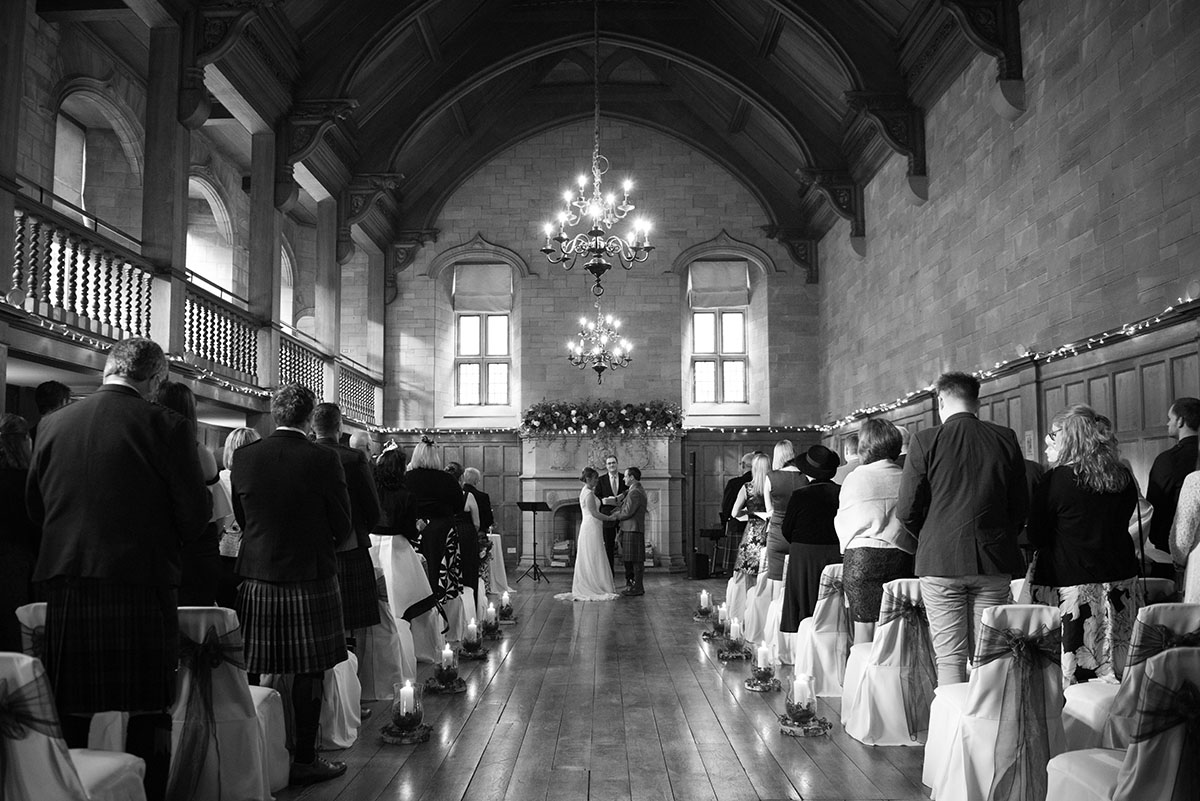 Wedding photography portfolio - a wedding ceremony taking place in a large hall with wooden ceiling and stone walls
