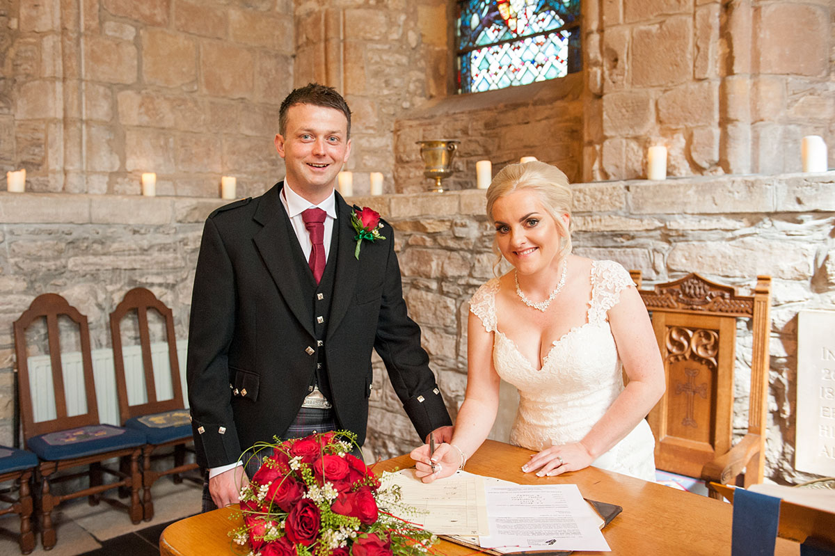 Wedding photography portfolio - bride and groom in a church standing at a wooden table and signing the marriage register