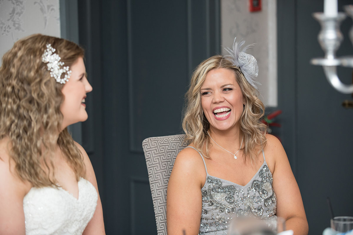 Wedding photos - bride looking at a woman in a grey dress with blonde hair, seated at a table and laughing