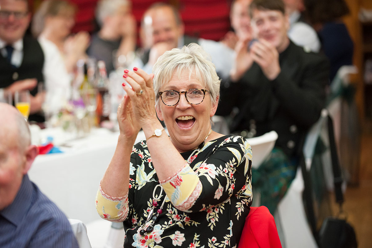 Wedding photos - candid image of a female wedding guest in a black floral dress smiling and clapping her hands