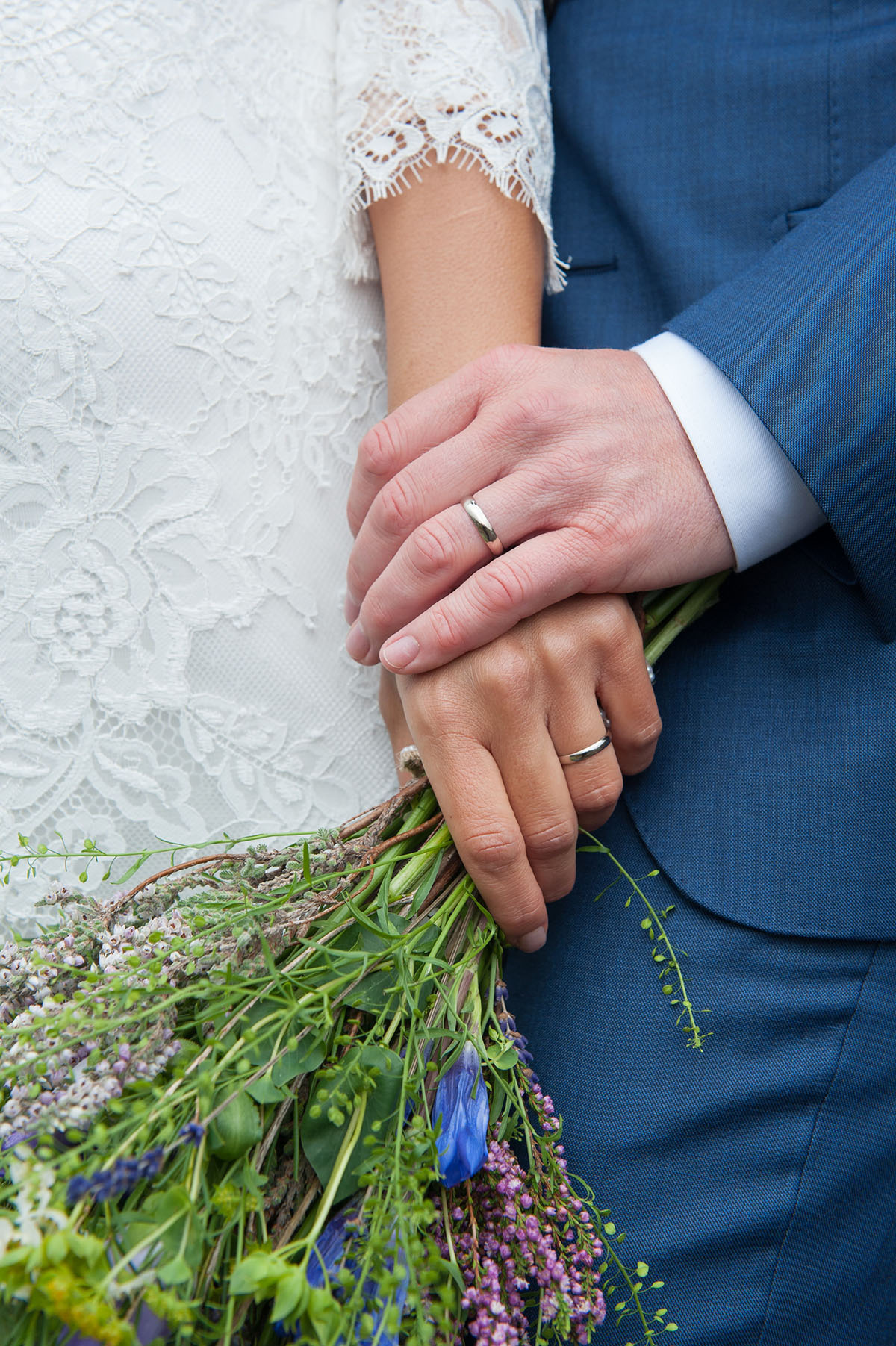 Wedding pictures - detailed image of wedding rings on the hands of a bride and groom, with the bride holding flowers