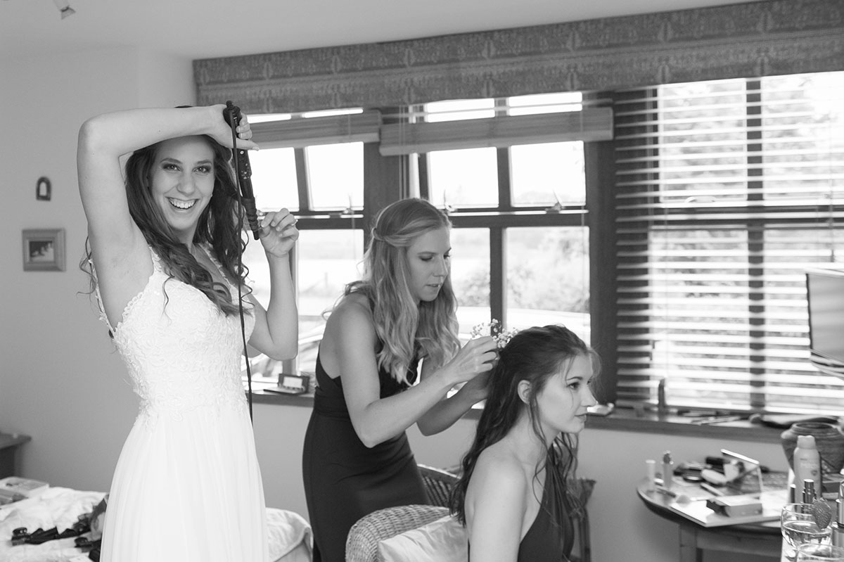 Wedding pictures - monochrome image of a bride in a white dress styling her hair with curlers, next to two bridesmaids
