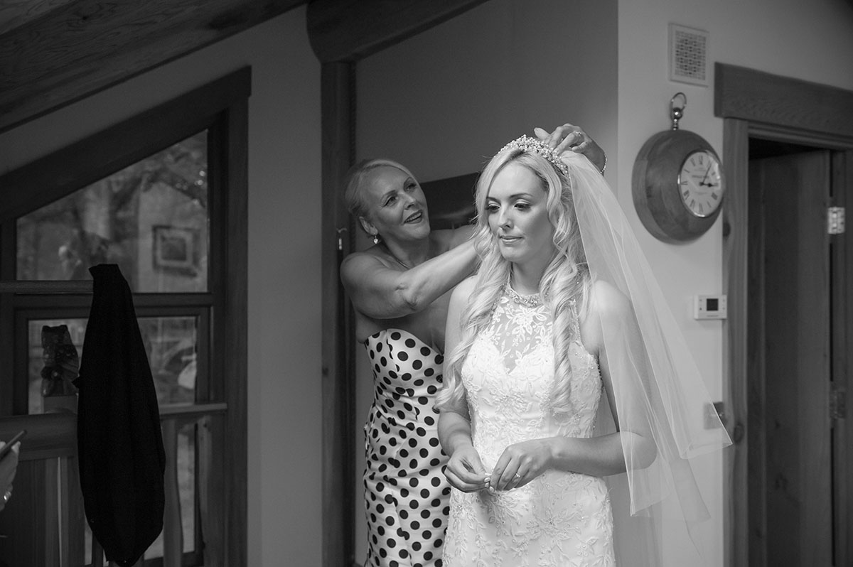 Wedding portfolio - monochrome image of mother-of-the-bride fitting a veil in a bride's long blonde hair