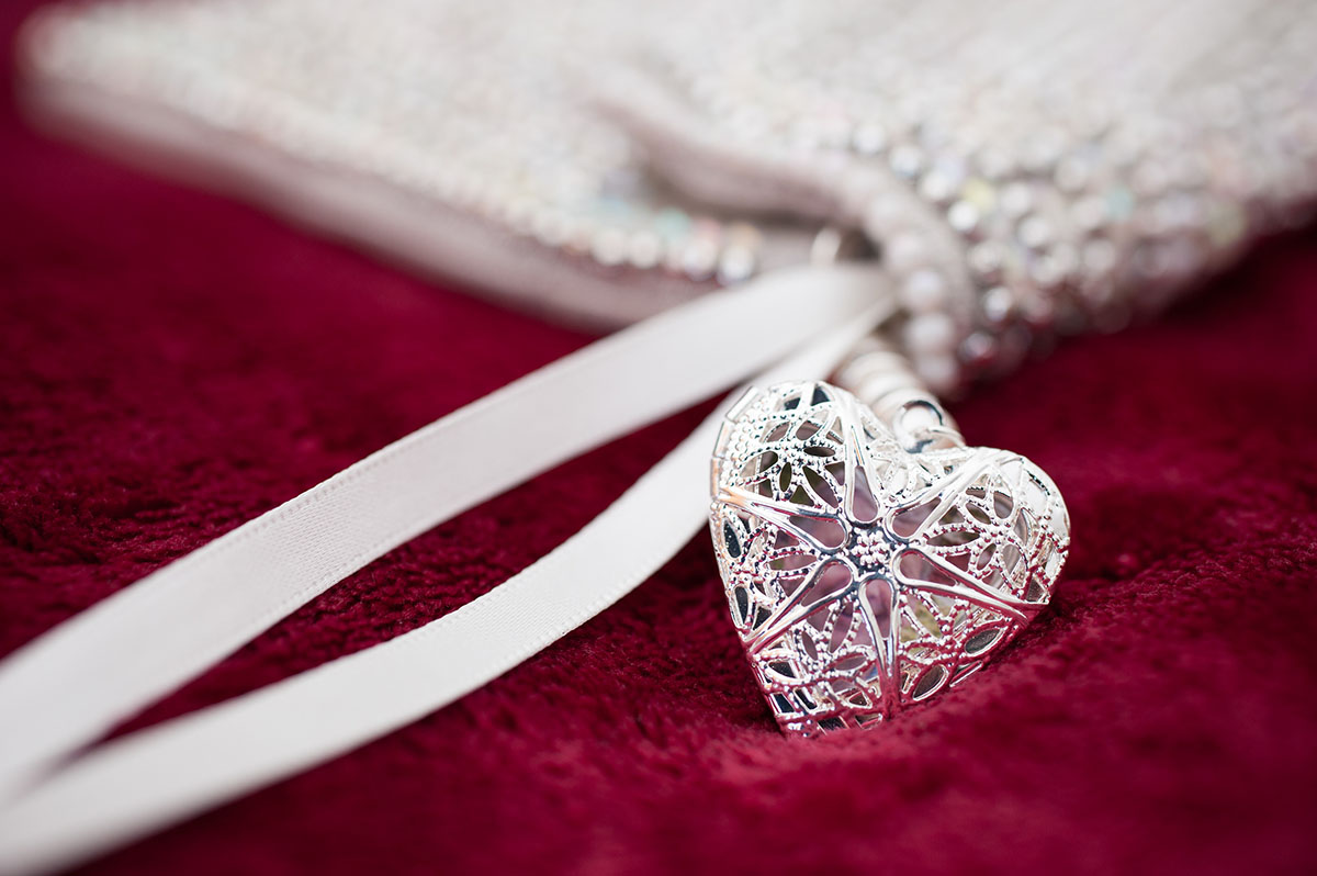 Wedding portfolio - heart shaped silver locket attached to a white beaded purse with ribbons sitting on red velvet