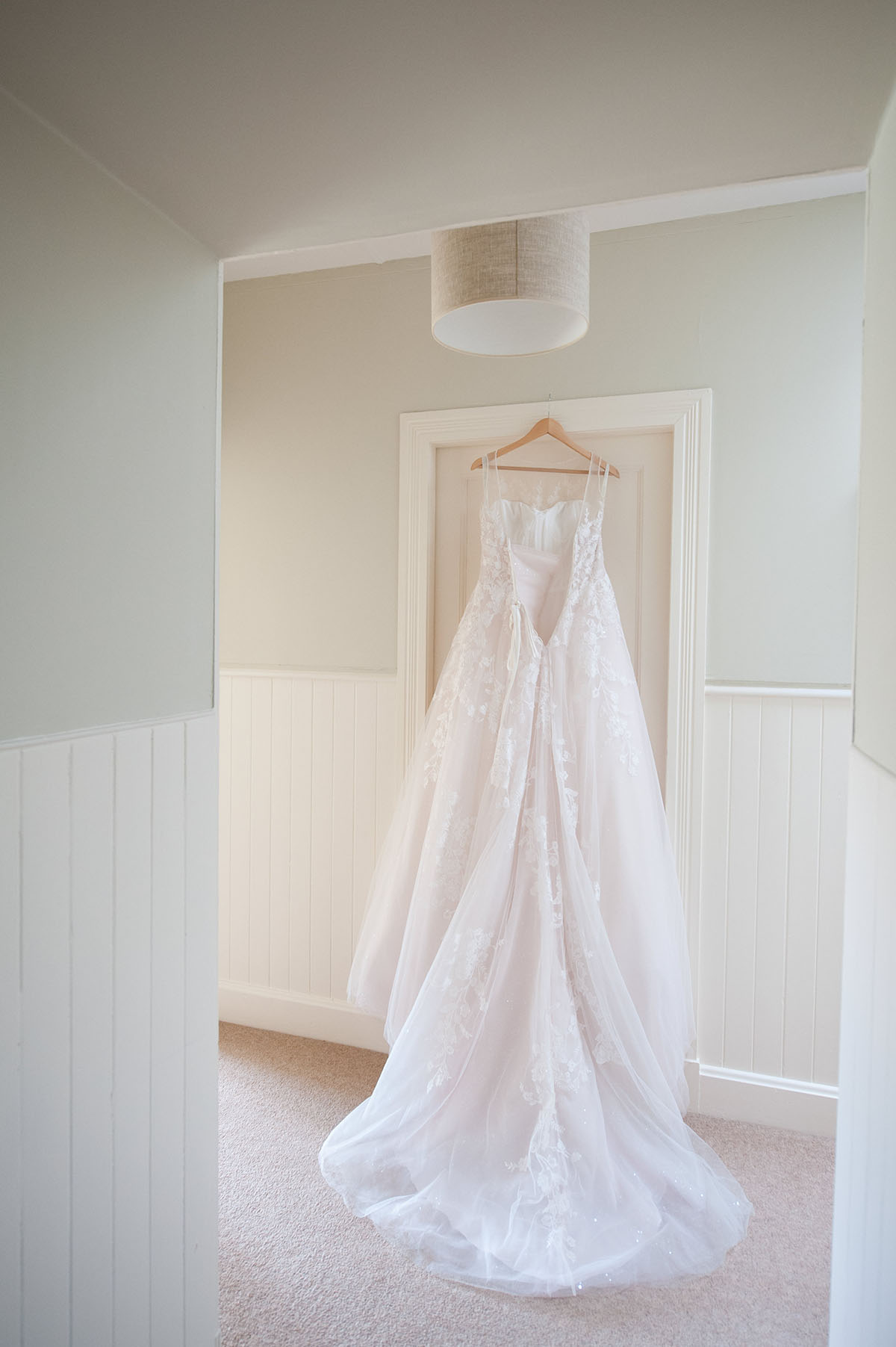 Wedding portfolio - back of a long white wedding dress, with the dress on a hanger hung over a white door frame