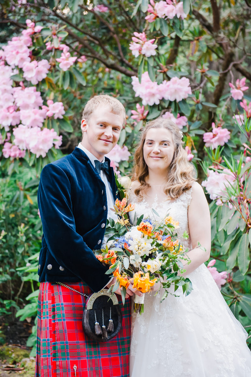 Bride and groom standing side by side and holding a bouquet of flowers, standing in front of a rhododendron bush in bloom