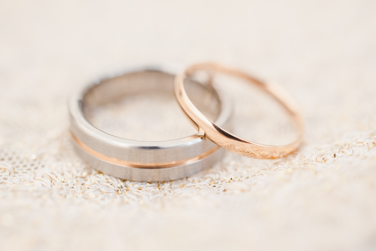 Matching wedding rings, one a gold band and the other a gold band between two silver bands, on a cream material