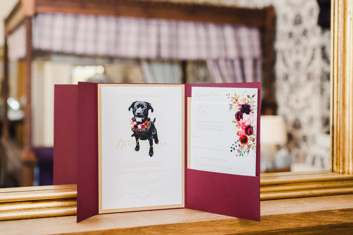 A white and burgundy wedding invitation featuring a black labrador in front of a mirror reflecting a four poster bed