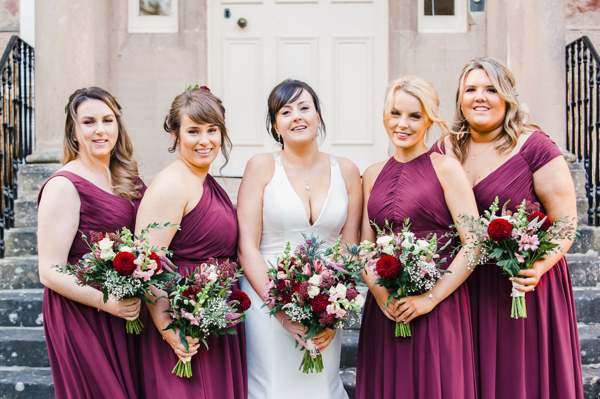 A wedding photo of a bride in white and her four bridesmaids in burgundy dresses, holding flowers, standing in front of steps