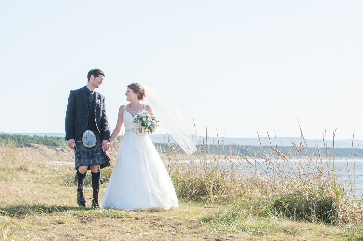 A bride and groom holding hands and smiling at each other while walking on grass with the sea, forestry and hills beyond