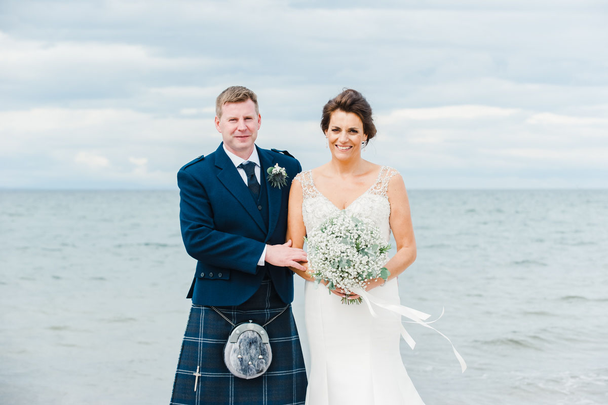 Wedding photograph of a bride and groom standing side by side, with the bride holding white flowers, with the sea behind them